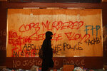 A person walks past a building covered with graffiti Thursday, May 28, 2020, in Minneapolis. Protests over the death of George Floyd, a black man who died in police custody Monday, broke out in Minneapolis for a third straight night. (AP Photo/John Minchillo)