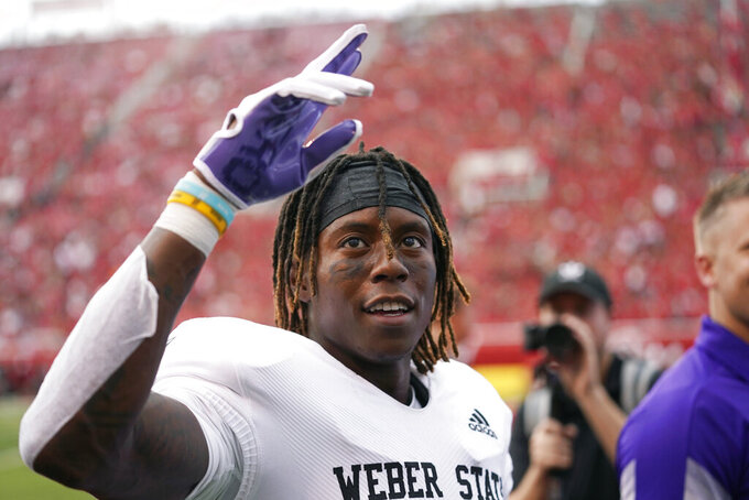 Weber State wide receiver Rashid Shaheed waves to the fans after scoring against Utah during the first half of NCAA college football game Thursday, Sept. 2, 2021, in Salt Lake City. (AP Photo/Rick Bowmer)