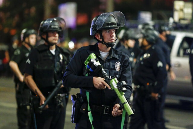 FILE — In this Nov. 4, 2020, file photo, police officers stand guard as they clear the streets during a protest in Los Angeles, following Tuesday's election. California organizations encompassing both police chiefs and rank-in-file officers proposed legislation in the wake of recent civil unrest that they they said would raise standards for police recruiting and training while increasing diversity, Thursday, Nov. 19, 2020. (AP Photo/Ringo H.W. Chiu, File)
