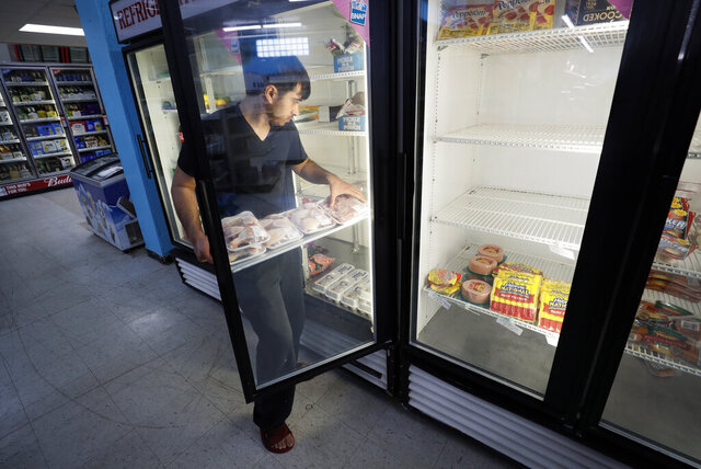 Hardik Kalra stocks meat in a cooler at a local super market, Friday, May 29, 2020, in Des Moines, Iowa. As if trips to the grocery store weren't nerve-racking enough, shoppers lately have seen the costs of meat, eggs and even potatoes soar as the coronavirus has disrupted processing plants and distribution networks. (AP Photo/Charlie Neibergall)