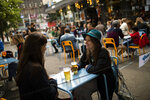 """In this Wednesday, June 10, 2020 photo, customers drinks beers at the terrace of the Bar du Matin restaurant in Brussels. Alex Van Tuijn, co-owner of four cafes in Brussels, has found that staying in business during a pandemic can mean sacrificing some of the very things a company is known for. His Bar du Matin, a stalwart in the nightlife in the Belgian capital city, is no longer serving breakfast and lunch despite the fact """"matin"""" is French for """"morning."""" (AP Photo/Francisco Seco)"""