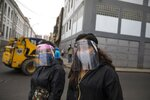 Women walk using masks and face shields required to travel in public transportation, in downtown Lima, Peru, Monday, Aug.3, 2020. (AP Photo/Rodrigo Abd)