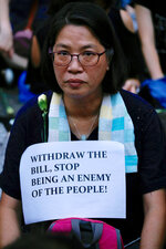 A woman joins hundreds of mothers protesting against the amendments to the extradition law after Wednesday's violent protest in Hong Kong on Friday, June 14, 2019. Calm appeared to have returned to Hong Kong after days of protests by students and human rights activists opposed to a bill that would allow suspects to be tried in mainland Chinese courts. (AP Photo/Vincent Yu)