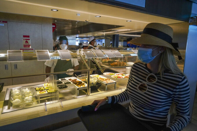 A passenger wears a face mask in a restaurant of the MSC Grandiosa cruise ship in Civitavecchia, near Rome, Wednesday, March 31, 2021. MSC Grandiosa, the world's only cruise ship to be operating at the moment, left from Genoa on March 30 and stopped in Civitavecchia near Rome to pick up more passengers and then sail toward Naples, Cagliari, and Malta to be back in Genoa on April 6. For most of the winter, the MSC Grandiosa has been a lonely flag-bearer of the global cruise industry stalled by the pandemic, plying the Mediterranean Sea with seven-night cruises along Italy's western coast, its major islands and a stop in Malta. (AP Photo/Andrew Medichini)