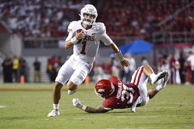 Texas quarterback Hudson Card (1) slips past Arkansas defensive back Grant Morgan (31) as he runs the ball during the second half of an NCAA college football game Saturday, Sept. 11, 2021, in Fayetteville, Ark. (AP Photo/Michael Woods)