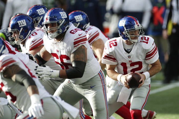 New York Giants quarterback Colt McCoy (12) drops to pass as offensive guard Shane Lemieux (66) blocks during the first half of an NFL football game against the Seattle Seahawks, Sunday, Dec. 6, 2020, in Seattle. (AP Photo/Larry Maurer)