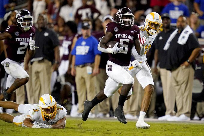 Texas A&M running back Devon Achane (6) escapes a tackle by Kent State safety Dean Clark (3) as he races for a touchdown during the second half of an NCAA college football game on Saturday, Sept. 4, 2021, in College Station, Texas. (AP Photo/Sam Craft)