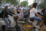 People wearing face masks to protect against the coronavirus wait at an intersection in Beijing, Wednesday, July 29, 2020. China reported more than 100 new cases of COVID-19 on Wednesday as the country continues to battle an outbreak in Xinjiang. (AP Photo/Mark Schiefelbein)
