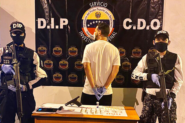 In this March 31, 2020, photo, Venezuelan police officers present a suspect arrested at a multiday party in Caracas, Venezuela, that violated Nicolas Maduro's order on large gatherings during the coronavirus pandemic. (Courtesy of Venezuelan Chief Prosecutor's Office via AP)