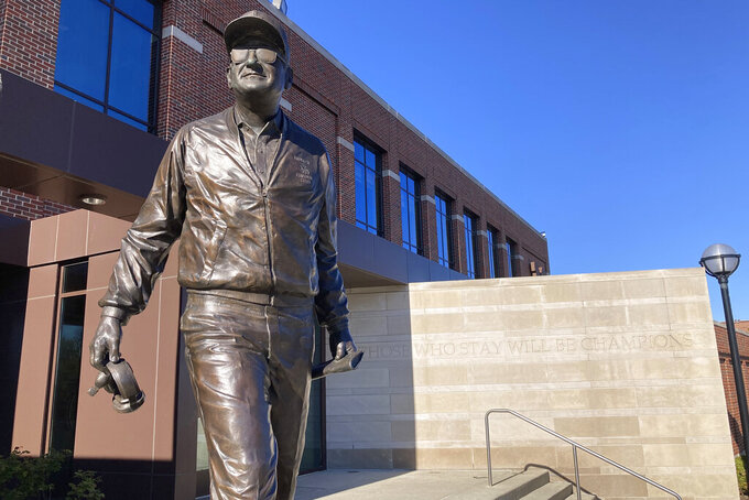 A statue of legendary football coach Bo Shembechler stands outside Schembechler Hall on the University of Michigan Campus in Ann Arbor, Mich., Wednesday,May 12, 2021. A report released Tuesday, May 11, 2021, about the stunning lack of action at the University of Michigan while a rogue doctor, Robert Anderson, was sexually assaulting hundreds of young men has pointed an unflattering light at one of the school's giants, the late football coach Bo Schembechler, whose bronze statue stands on campus. (AP Photo/Mike Householder)