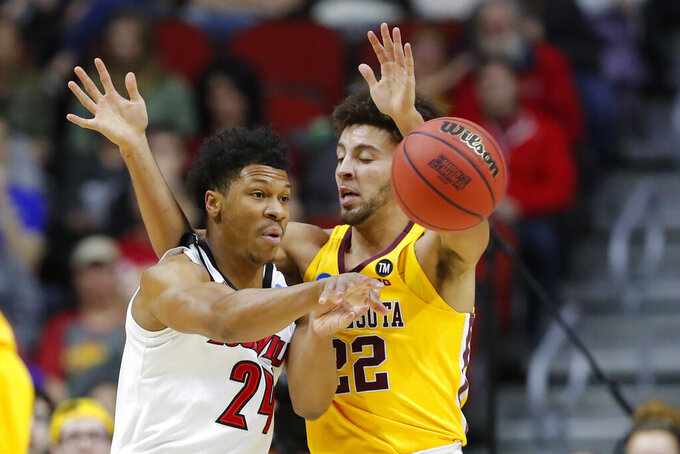 Louisville forward Dwayne Sutton passes around Minnesota guard Gabe Kalscheur, right, during a first round men's college basketball game in the NCAA Tournament, Thursday, March 21, 2019, in Des Moines, Iowa. (AP Photo/Charlie Neibergall)