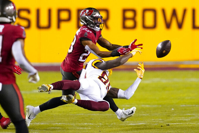 Washington Football Team wide receiver Cam Sims (89) drops a ball while being covered by Tampa Bay Buccaneers cornerback Sean Murphy-Bunting (23) during the first half of an NFL wild-card playoff football game, Saturday, Jan. 9, 2021, in Landover, Md. (AP Photo/Andrew Harnik)