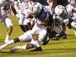 Virginia running back Wayne Taulapapa (21) scores a touchdown while defended by Old Dominion safety Calvin Brewton (4) and cornerback Geronda Hall (23) during the first quarter of an NCAA college football game in Charlottesville, Va., Saturday, Sept. 21, 2019. (AP Photo/Andrew Shurtleff)