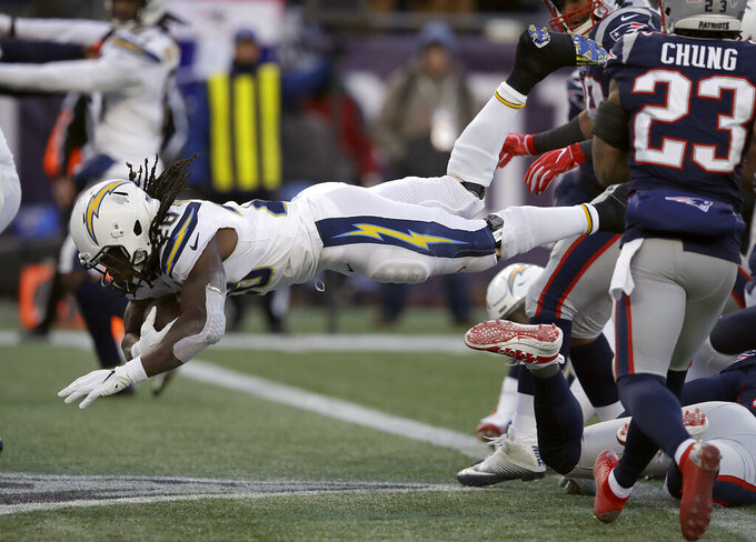 Los Angeles Chargers running back Melvin Gordon, left, dives into the end zone for a touchdown during the second half of an NFL divisional playoff football game against the New England Patriots, Sunday, Jan. 13, 2019, in Foxborough, Mass. (AP Photo/Charles Krupa)