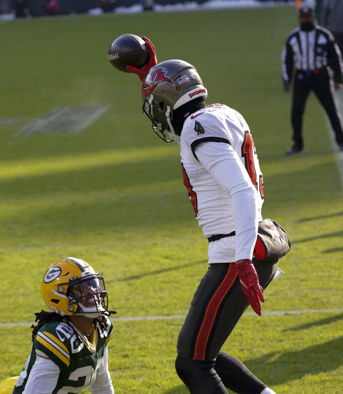 Tampa Bay Buccaneers' Mike Evans holds up the ball after catching a 15-yard touchdown pass against Green Bay Packers' Kevin King during the first half of the NFC championship NFL football game in Green Bay, Wis., Sunday, Jan. 24, 2021.(AP Photo/Jeffrey Phelps)