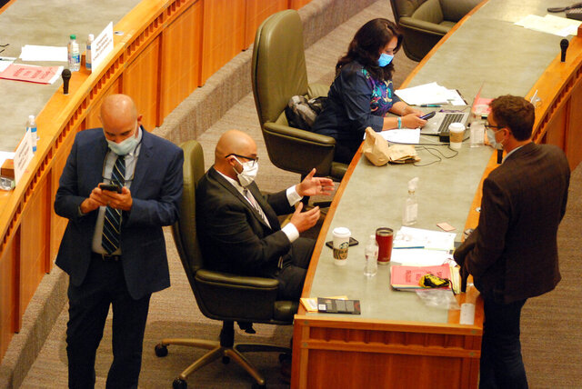 Democratic New Mexico state Rep. Javier Martinez, center, of Albuquerque, and Republican Rep. Gregg Schmedes, right, of Tijeras, converse Saturday, June 20, 2020, on the floor of the New Mexico House of Representatives in Santa Fe. The New Mexico Legislature met in a special session to address a gaping budget hole linked to the coronavirus and related economic upheaval. (AP Photo/Morgan Lee)