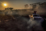 Redwan Hoff sits on the roof of a BMW while driver Lorenzo Dada competes in the Redbull Shay iMoto, a spinning event where twelve of the best spinners from South Africa gather to showcase their spinning skills and stunts in Johannesburg, Friday, Sept 10, 2021. (AP Photo/Shiraaz Mohamed.