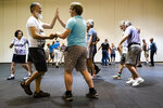 This July 3, 2019 photo shows Jorge Velasquez of Toronto, left, and Matthew Lytthouse, of Vermont, during the annual International Association of Gay Square Dance Clubs convention in Philadelphia. The Independence Squares were founded 30 years ago in part as a social outlet for the LGBTQ community. (AP Photo/Matt Rourke)