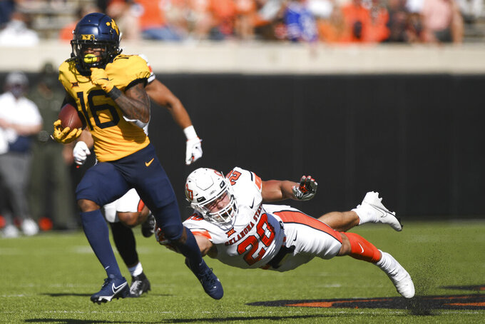 Oklahoma State linebacker Malcolm Rodriguez (20) falls short of stopping West Virginia wide receiver Winston Wright Jr. (16) as he runs for a touchdown during an NCAA college football game Saturday, Sept. 26, 2020, in Stillwater, Okla. (AP Photo/Brody Schmidt)