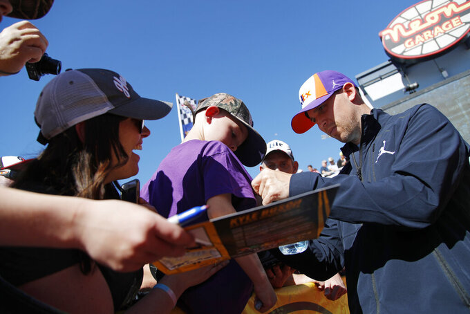 Denny Hamlin gives autographs to fans before a NASCAR Cup Series auto race at Las Vegas Motor Speedway, Sunday, March 3, 2019, in Las Vegas. (AP Photo/John Locher)