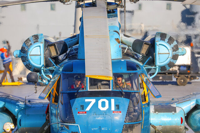 This image released Thursday, Jan. 14, 2021, by the Iranian Army shows a helicopter on an Iranian-made Makran logistics vessel during a naval drill. Iran fired cruise missiles Thursday as part of the drill in the Gulf of Oman, state media reported, amid heightened tensions with the U.S. (Iranian Army via AP)