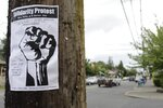 A sign advertising a daily protest in solidarity with Black Lives Matter is affixed to a telephone pole in a historically Black neighborhood in Portland, Ore., on Wednesday, July 1 2020. Thousands of protesters in the liberal and predominantly white city have taken to the streets peacefully every day for more than five weeks to decry police brutality, but recent violence by smaller groups is creating a deep schism in the protest movement and prompting allegations that white protesters are co-opting the moment. (AP Photo/Gillian Flaccus)