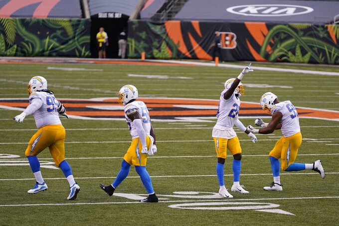 Los Angeles Chargers' Linval Joseph (95), Kenneth Murray (56), Brandon Facyson (28) and Jerry Tillery (99) celebrate after defeating the Cincinnati Bengals an NFL football game, Sunday, Sept. 13, 2020, in Cincinnati. Los Angeles won 16-13. (AP Photo/Bryan Woolston)