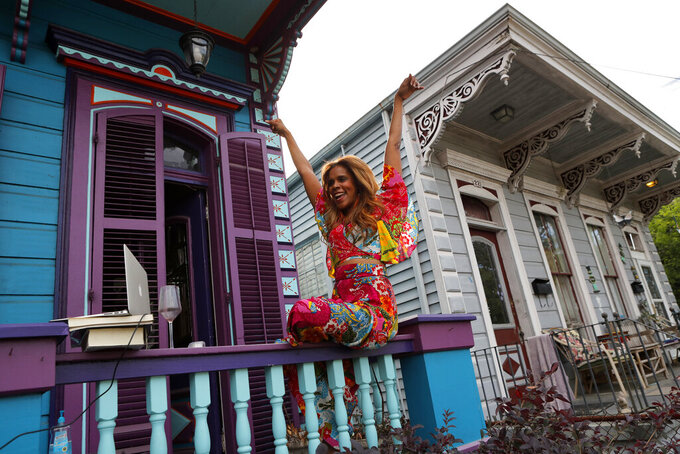 Anais St. John reacts after conducting a front porch concert at her home in New Orleans, Saturday, April 11, 2020. With New Orleans music venues shuttered for more than a month now because of the coronavirus outbreak, musicians and fans are finding new places to connect – porches, living rooms, studios and lawns – and reaching their largest audiences online, many streaming performances live on social media platforms. But for the city's club owners awaiting the green light to reopen there's concern about all the uncertainties, like how long it may take tourists to return, how soon the music scene will rebound and when it does, what it will look like. (AP Photo/Gerald Herbert)