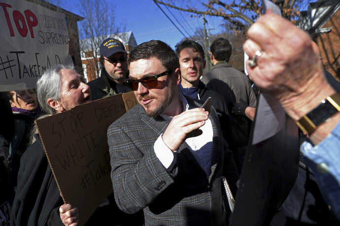 """FILE - In this Feb. 27, 2018, file photo, Jason Kessler walks through a crowd of protesters in front of the Charlottesville Circuit Courthouse ahead of a decision regarding the covered Confederate statues, during a rally in Charlottesville, Va. Kessler, an organizer of a white nationalist rally that erupted in violence in Virginia last summer has agreed to """"actively discourage"""" armed paramilitary activity at any future rallies in Charlottesville, under an agreement filed in court Thursday, July 12. (Zack Wajsgras/The Daily Progress via AP, File)"""