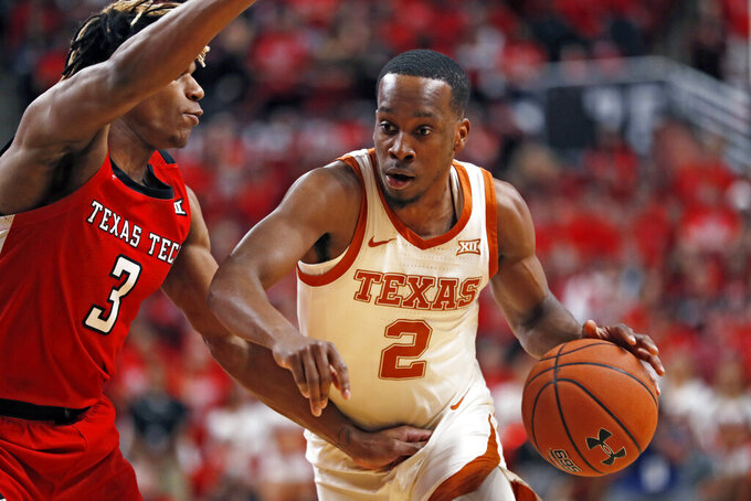 Texas' Matt Coleman III (2) drives the ball around Texas Tech's Jahmi'us Ramsey (3) during the first half of an NCAA college basketball game Saturday, Feb. 29, 2020, in Lubbock, Texas. (AP Photo/Brad Tollefson)