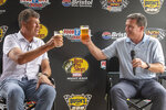 Michael Waltrip, left, and Bristol Motor Speedway's Executive Vice President and General Manager Jerry Caldwell raise a glass as they talk about the upcoming racing at Bristol Motor Speedway while visiting Michael Waltrip Brewing, Wednesday, Sept. 1, 2021, in Bristol, Va. (David Crigger/Bristol Herald Courier via AP)