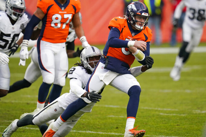 Las Vegas Raiders outside linebacker Cory Littleton (42) tries to tackles Denver Broncos quarterback Drew Lock (3) during the first half of an NFL football game, Sunday, Jan. 3, 2021, in Denver. (AP Photo/David Zalubowski)