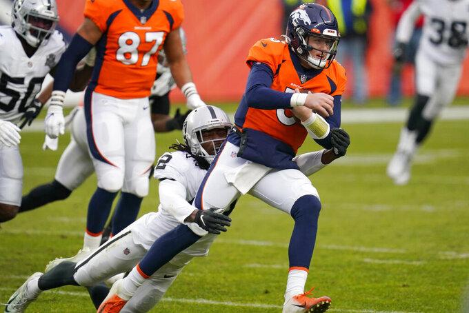 Las Vegas Raiders outside linebacker Cory Littleton (42) tries to tackles Denver Broncos quarterback Drew Lock (3) during the first half of an NFL football game, Sunday, Jan. 3, 2021, in Denver. (AP Photo/David Zalubowski)