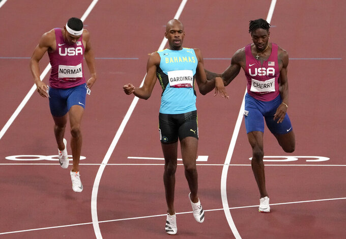 Steven Gardiner, of Bahamas wins the gold medal ahead Michael Cherry, of United States, fourth, and Michael Norman, of United States, fifth, in the final of the men's 400-meter at the 2020 Summer Olympics, Thursday, Aug. 5, 2021, in Tokyo, Japan. (AP Photo/Charlie Riedel)