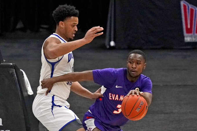 Evansville's Jawaun Newton (3) dribbles as Indiana State's Tre Williams defends during the second half of an NCAA college basketball game in the quarterfinal round of the Missouri Valley Conference men's tournament Friday, March 5, 2021, in St. Louis. (AP Photo/Jeff Roberson)