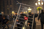 Demonstrators throw metallic fences against police during clashes in downtown Barcelona, Spain, Friday, Oct. 30, 2020. Clashes have erupted in a central Barcelona square between anti-riot police and hundreds who had gathered to protest the mandatory closure of bars, restaurants and other businesses in the latest effort to rein in on coronavirus outbreaks. (AP Photo/Emilio Morenatti)