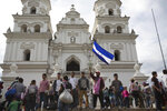 Honduran migrants stand outside a Catholic church, one waving his nation's flag, before starting to walk again as part of a caravan of hundreds of Honduran migrants making their way the U.S. in Esquipulas, Guatemala, early Tuesday, Oct. 16, 2018. U.S. President Donald Trump threatened on Tuesday to cut aid to Honduras if it doesn't stop the impromptu caravan of migrants, but it remains unclear if governments in the region can summon the political will to physically halt the determined border-crossers. (AP Photo/Moises Castillo)