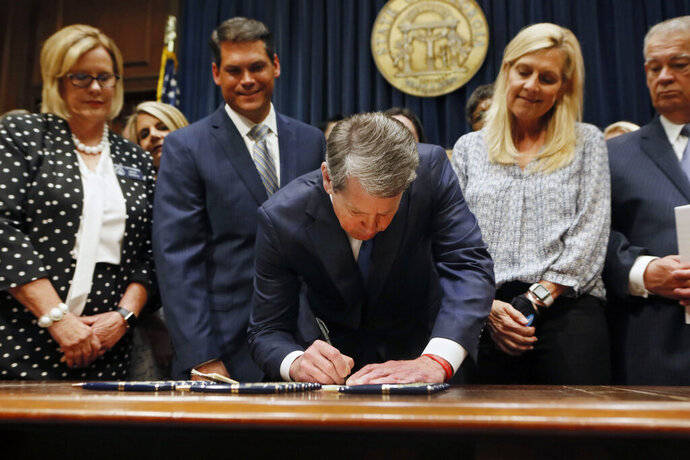"FILE - Georgia's Republican Gov. Brian Kemp, center, signs legislation Tuesday, May 7, 2019, in Atlanta, banning abortions once a fetal heartbeat can be detected, which can be as early as six weeks before many women know they're pregnant. A federal judge is permanently blocking Georgia's 2019 ""heartbeat"