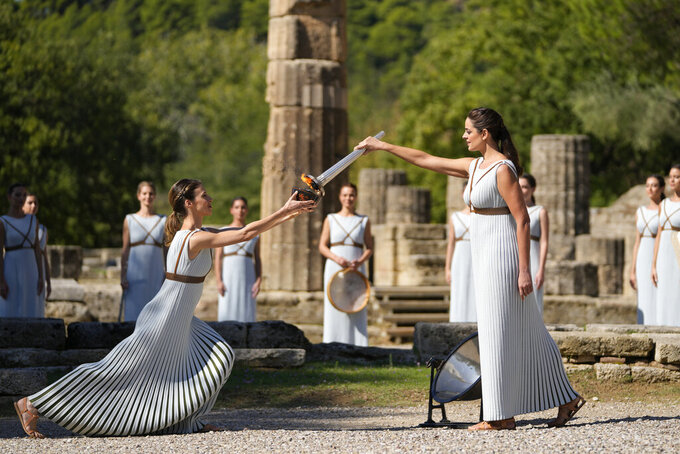 Greek actress Xanthi Georgiou, right, playing the role of the High Priestess, holds the torch during the lighting of the Olympic flame at Ancient Olympia site, birthplace of the ancient Olympics in southwestern Greece, Monday, Oct. 18, 2021. The flame will be transported by torch relay to Beijing, China, which will host the Feb. 4-20, 2022 Winter Olympics. (AP Photo/Thanassis Stavrakis)