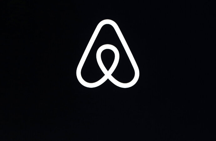 FILE - This Feb. 22, 2018, file photo shows an Airbnb logo during an event in San Francisco. A lucky few will be able to live the adventures of Phileas Fogg from Jules Vernes' classic