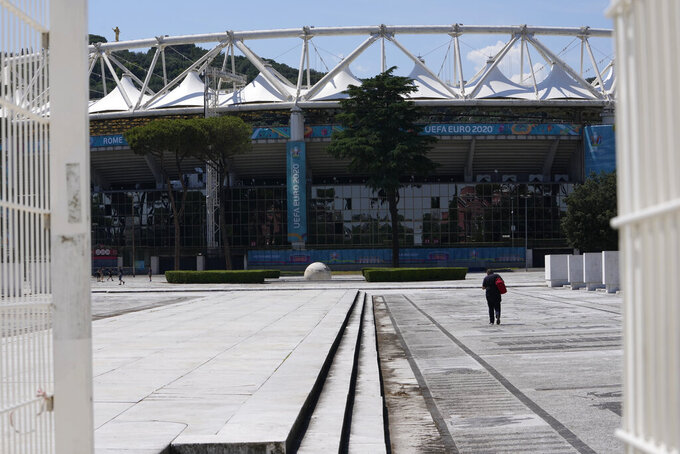 A man walks in front of Rome's Olympic stadium, Wednesday, June 9, 2021. The Euro 2020 gets underway on Friday June 11 and is being played in 11 host cities across 11 countries. (AP Photo/Alessandra Tarantino)