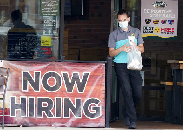 FILE - In this Sept. 2, 2020 file photo, a customer wears a face mask as they carry their order past a now hiring sign at an eatery in Richardson, Texas. The number of Americans seeking unemployment benefits fell last week to 751,000, the lowest since March, but it's still historically high and indicates the viral pandemic is still forcing many employers to cut jobs. (AP Photo/LM Otero, File)