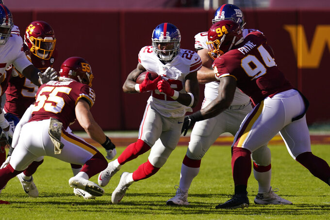 New York Giants running back Wayne Gallman (22) runs with the ball against Washington Football Team linebacker Cole Holcomb (55) and Washington Football Team defensive tackle Daron Payne (94) in the first half of an NFL football game, Sunday, Nov. 8, 2020, in Landover, Md. (AP Photo/Patrick Semansky)