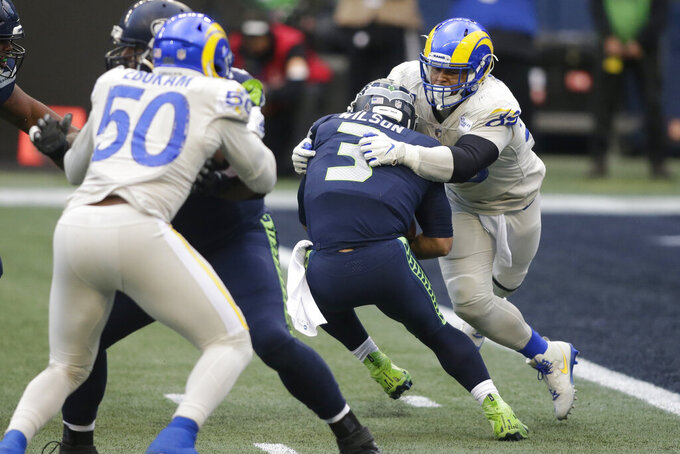 Seattle Seahawks quarterback Russell Wilson (3) is sacked by Los Angeles Rams defensive lineman Aaron Donald (99), right, during the second half of an NFL football game, Sunday, Dec. 27, 2020, in Seattle. (AP Photo/Scott Eklund)
