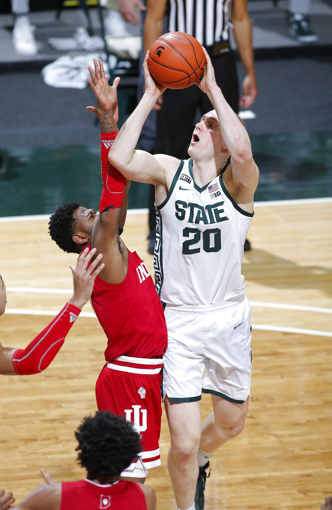 Michigan State's Joey Hauser, right, shoots against Indiana's Aljami Durham during the second half of an NCAA college basketball game Tuesday, March 2, 2021, in East Lansing, Mich. Michigan State won 64-58. (AP Photo/Al Goldis)