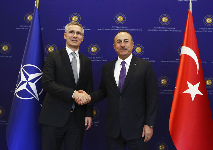 Turkey's Foreign Minister Mevlut Cavusoglu, right, shakes hands with NATO Secretary General Jens Stoltenberg, prior to their meeting in Ankara, Turkey, Monday, April 16, 2018. (Pool Photo via AP)