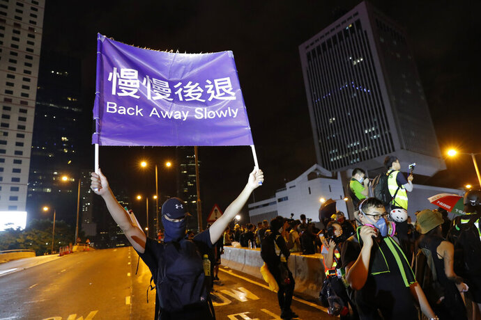 A demonstrator holds up a sign reading