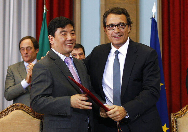FILE - In this Dec. 30, 2011 file photo, Cao GuangJing, left, CEO of China Three Gorges Corporation, embraces Antonio Mexia, CEO of Energia de Portugal (EDP) after signing a deal at the Portuguese Finance Ministry in Lisbon. The Lisbon stock exchange on Monday july 6, 2020, suspended trading in Portugal's national energy provider EDP and its international renewable energy division after media reports said a magistrate has suspended the CEOs of both companies amid a major corruption investigation. EDP is one of Portugal's biggest companies, with significant interests in the U.S. renewable energy market. Its biggest shareholder is China Three Gorges. (AP Photo/ Francisco Seco)