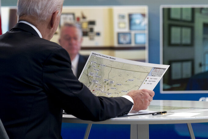 President Joe Biden looks at a map of wildfires in Montana as he speaks with governors about ongoing efforts to strengthen wildfire prevention, preparedness and response efforts, and hear firsthand about the ongoing impacts of the 2021 wildfire season in the South Court Auditorium in the Eisenhower Executive Office Building on the White House Campus in Washington, Friday, July 30, 2021. (AP Photo/Andrew Harnik)