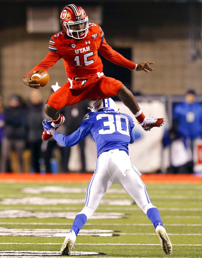 FILE - In this Saturday, Nov. 24, 2018, file photo, Utah quarterback Jason Shelley (15) hurdles BYU defensive back Keenan Ellis (30) in the first half of an NCAA college football game in Salt Lake City. One quality that teammates and coaches love about Utah quarterback Jason Shelley is his confidence. The moment is never too big for the redshirt freshman. (AP Photo/Rick Bowmer, File)